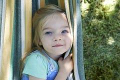 Портрет белокурой девушки ребенка, ослабляя на красочном гамаке Стоковое фото RF