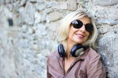 Портрет белокурой женщины усмехаясь с наушниками к шеи Стоковая Фотография