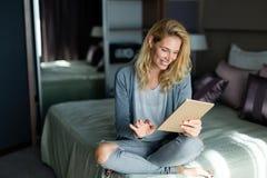 Портрет белокурой красивой женщины используя таблетку Стоковое Фото