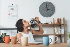 портрет бизнесмена в кофе нижнего белья выпивая от бака кофе на рабочем месте с таблеткой Стоковая Фотография