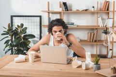 портрет бизнесмена в кофе нижнего белья выпивая пока работающ на компьтер-книжке на рабочем месте Стоковая Фотография RF