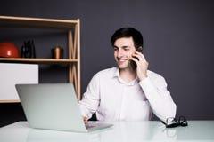 Портрет бизнесмена говоря на мобильном телефоне в офисе над компьтер-книжкой Стоковые Фотографии RF