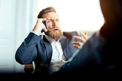 Портрет бизнесмена говоря на мобильном телефоне в офисе Стоковое Фото