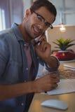 Портрет бизнесмена говоря на мобильном телефоне на творческом офисе Стоковые Изображения RF