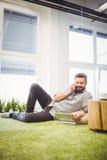 Портрет бизнесмена говоря на телефоне пока использующ компьтер-книжку на творческом офисе Стоковые Фото