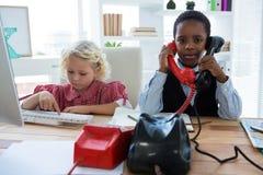 Портрет бизнесмена говоря на телефоне пока коллега используя компьютер Стоковая Фотография