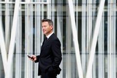 Портрет бизнесмена думая и держа мобильный телефон стоковое изображение