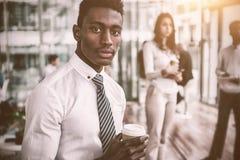 Портрет бизнесмена держа устранимую кофейную чашку Стоковое Изображение