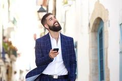 Портрет бизнесмена идя в город держа мобильный телефон стоковое изображение rf