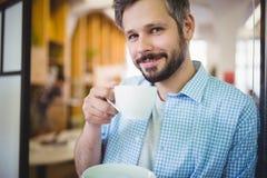 Портрет бизнесмена имея кофе на столовой офиса Стоковое фото RF