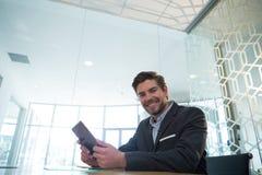 Портрет бизнесмена используя цифровую таблетку на столе Стоковые Изображения