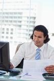 Портрет бизнесмена используя компьютер пока смотрящ stat Стоковая Фотография RF