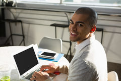 Портрет бизнесмена используя портативный компьютер пока сидящ на столе Стоковые Изображения RF