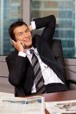 Портрет бизнесмена используя телефон в офисе, усмехаясь Стоковые Изображения RF