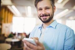Портрет бизнесмена используя телефон в столовой офиса Стоковая Фотография RF