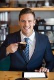 Портрет бизнесмена используя цифровую таблетку в café Стоковое Фото