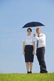 Портрет бизнесмена и коммерсантка под зонтиком в парке Стоковая Фотография RF