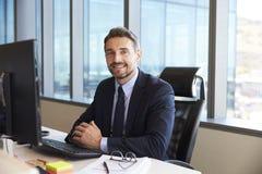 Портрет бизнесмена на столе офиса используя компьютер Стоковое Фото