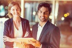 Портрет бизнесмена обсуждая с коллегой над цифровой таблеткой Стоковое Фото