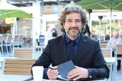 Портрет бизнесмена писать обработку документов вне офиса на кафе outdoors принимать человека принципиальной схемы кофе пролома Стоковые Фотографии RF
