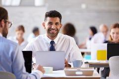 Портрет бизнесмена работая на компьтер-книжке в занятом офисе Стоковое Изображение RF