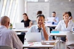 Портрет бизнесмена работая на компьтер-книжке в занятом офисе Стоковые Фото