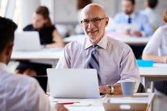 Портрет бизнесмена работая на компьтер-книжке в занятом офисе Стоковое Фото