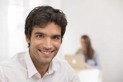 Портрет бизнесмена работая на компьютере в офисе, смотря c Стоковые Фото