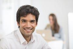 Портрет бизнесмена работая на компьютере в офисе, смотря c Стоковое Изображение RF