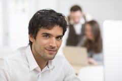 Портрет бизнесмена работая на компьютере в офисе, смотря c Стоковая Фотография