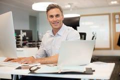 Портрет бизнесмена работая на компьютере в офисе Стоковое фото RF