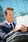 Портрет бизнесмена работая на таблетке outdoors Стоковые Фотографии RF