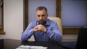 портрет бизнесмена серьезный Директор в голубой рубашке сидя на столе офиса, смотря камеру акции видеоматериалы