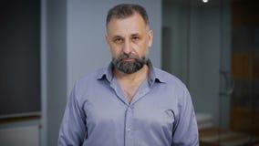портрет бизнесмена серьезный Человек в голубой рубашке стоя в коридоре, смотря камеру акции видеоматериалы