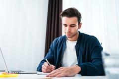 Портрет бизнесмена сидя на ноутбуке и блокноте пользы таблицы в размерах офиса стоковая фотография
