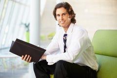 Портрет бизнесмена сидя на отчете о Рединга софы Стоковые Изображения RF