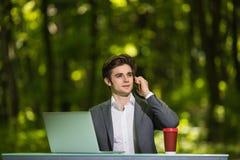 Портрет бизнесмена сидя на работе стола офиса на мобильном телефоне портативного компьютера и чашки кофе говоря на дороге зеленог Стоковая Фотография RF