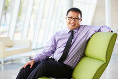 Портрет бизнесмена сидя на софе в самомоднейшем офисе Стоковое Изображение RF