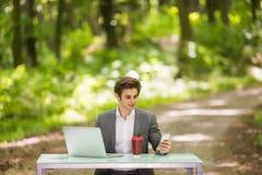 Портрет бизнесмена сидя на столе офиса с мобильным телефоном портативного компьютера и чашки кофе говоря в зеленом равенстве леса Стоковая Фотография RF