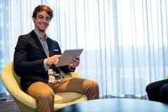 Портрет бизнесмена сидя на софе и используя компьтер-книжку Стоковая Фотография