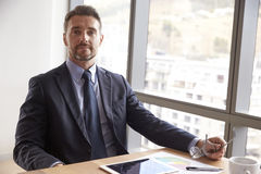 Портрет бизнесмена сидя на столе с таблеткой цифров Стоковые Фото