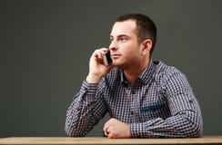 Портрет бизнесмена сидя на таблице Стоковая Фотография