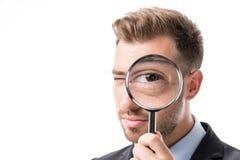 портрет бизнесмена смотря камеру через лупу Стоковые Изображения RF