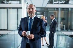 Портрет бизнесмена стоя в коридоре и коллегах говоря в предпосылке Стоковые Фотографии RF