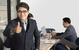 Портрет бизнесмена стоя перед ее командой на офисе, азиатском бизнесмене водя ее команду Стоковое Изображение RF