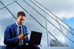 Портрет бизнесмена с компьтер-книжкой, говоря на мобильном телефоне B Стоковые Фото