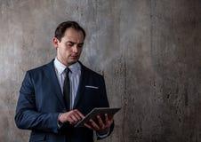 Портрет бизнесмена с таблеткой на конкретной серой предпосылке стены Стоковое фото RF