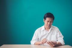 Портрет бизнесмена усмехаясь и используя пусковую площадку на настольном компьютере против голубой стены Стоковые Изображения RF