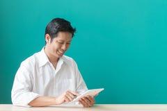 Портрет бизнесмена усмехаясь и используя пусковую площадку на настольном компьютере против голубой стены Стоковое Фото