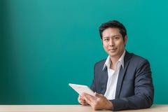 Портрет бизнесмена усмехаясь и используя пусковую площадку на настольном компьютере против голубой стены Стоковые Фото